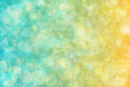 Background with gradients from yellow to cyan colors and circle shaped bokeh spots on it. 版權商用圖片
