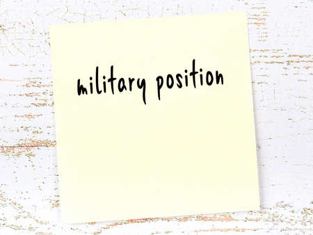 Concept of reminder about military position. Yellow sticky sheet of paper on wooden wall with inscription