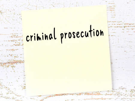 Concept of reminder about criminal prosecution. Yellow sticky sheet of paper on wooden wall with inscription 版權商用圖片