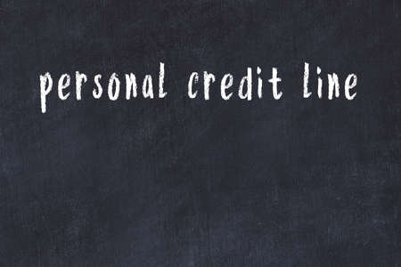 Chalk handwritten inscription personal credit line on black desk