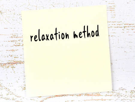 Yellow sticky note on wooden wall with handwritten inscription relaxation method