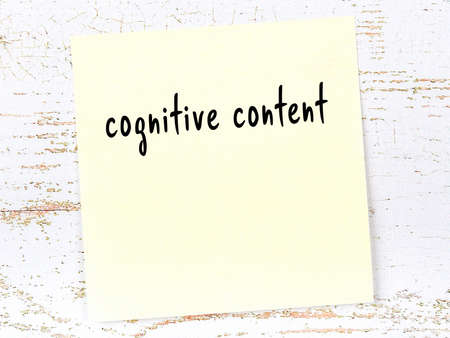 Concept of reminder about cognitive content. Yellow sticky sheet of paper on wooden wall with inscription