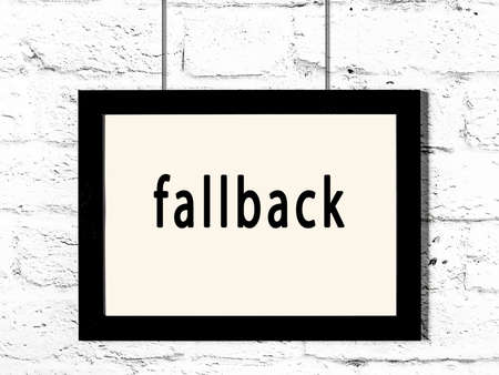 Black wooden frame with inscription fallback hanging on white brick wall