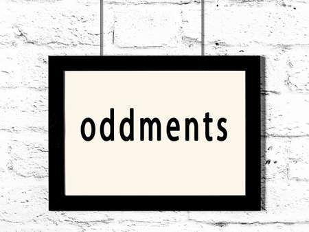 Black wooden frame with inscription oddments hanging on white brick wall 版權商用圖片