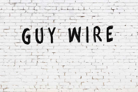 White brick wall with inscription guy wire handwritten with black paint