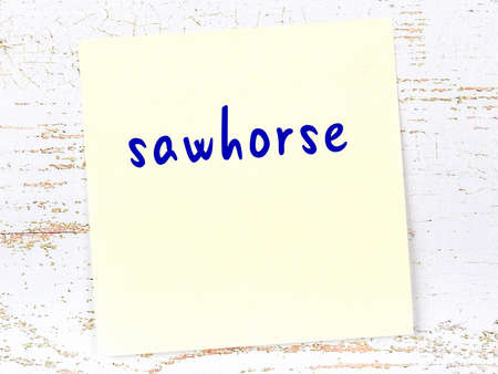 Concept of reminder about sawhorse. Yellow sticky sheet of paper on wooden wall with inscription