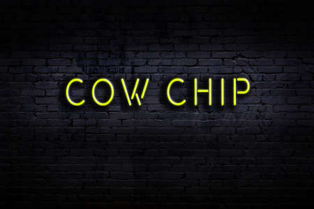 Neon sign with inscription cow chip against brick wall. Night view