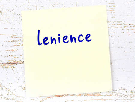 Concept of reminder about lenience. Yellow sticky sheet of paper on wooden wall with inscription