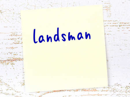 Concept of reminder about landsman. Yellow sticky sheet of paper on wooden wall with inscription
