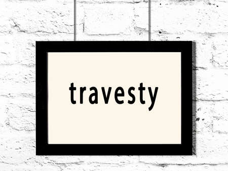 Black wooden frame with inscription travesty hanging on white brick wall 版權商用圖片