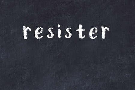 Chalk handwritten inscription resister on black desk Фото со стока