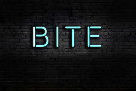 Neon sign with inscription bite against brick wall. Night view