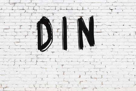 Inscription din written with black paint on white brick wall. Stock Photo