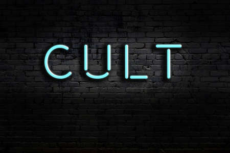 Neon sign with inscription cult against brick wall. Night view