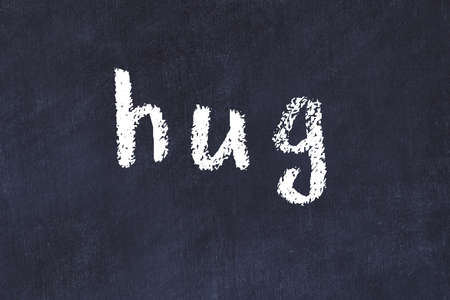 Chalk handwritten inscription hug on black desk