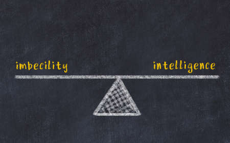 Concept of balance between imbecility and intelligence. Black chalboard with sketch of scales and words on it 版權商用圖片