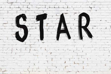 Inscription star written with black paint on white brick wall. 版權商用圖片