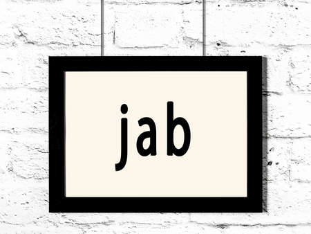 Black wooden frame with inscription jab hanging on white brick wall Imagens