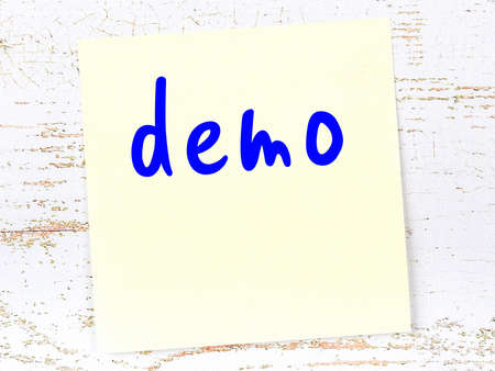 Yellow sticky note on wooden wall with handwritten inscription demo Imagens