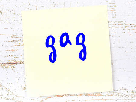 Concept of reminder about gag. Yellow sticky sheet of paper on wooden wall with inscription Stockfoto