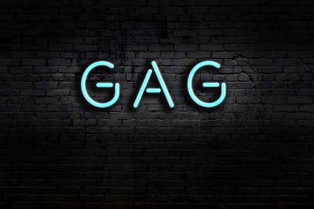 Neon sign on brick wall at night. Inscription gag Imagens