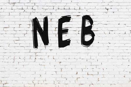 Inscription neb written with black paint on white brick wall.