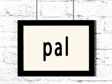 Black wooden frame with inscription pal hanging on white brick wall