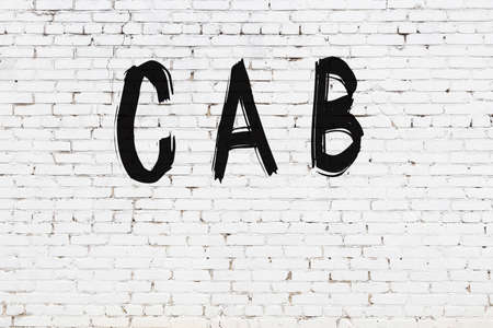 White brick wall with inscription cab handwritten with black paint