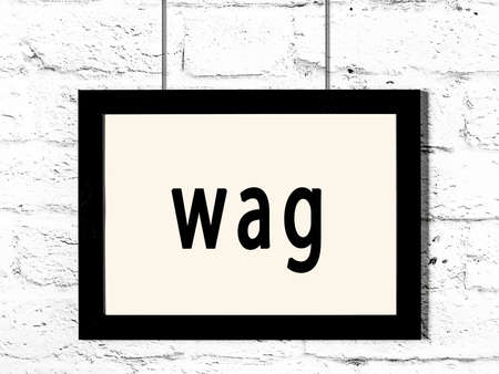 Black wooden frame with inscription wag hanging on white brick wall