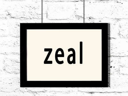 Black wooden frame with inscription zeal hanging on white brick wall Imagens