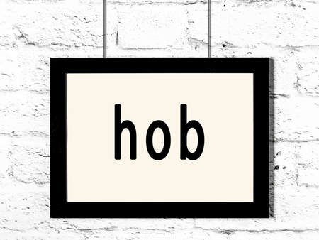 Black wooden frame with inscription hob hanging on white brick wall