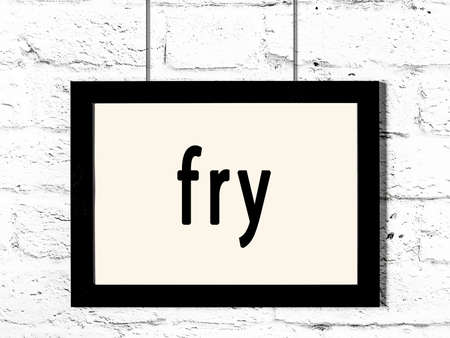 Black wooden frame with inscription fry hanging on white brick wall Imagens