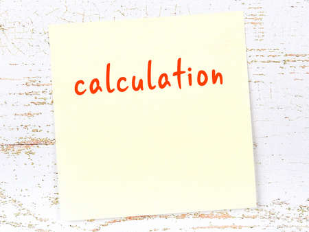 Concept of reminder about calculation. Yellow sticky sheet of paper on wooden wall with inscription