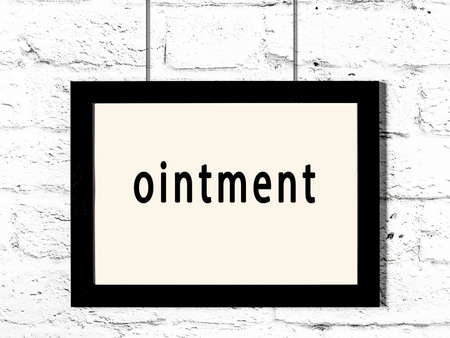 Black wooden frame with inscription ointment hanging on white brick wall