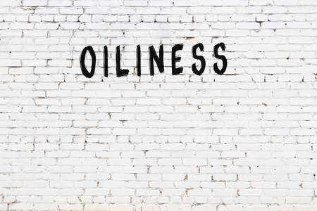 Inscription oiliness written with black paint on white brick wall.