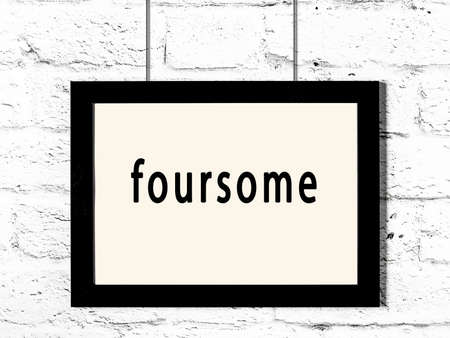 Black wooden frame with inscription foursome hanging on white brick wall