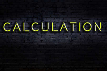 Neon sign on brick wall at night. Inscription calculation