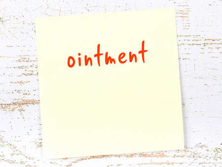 Yellow sticky note on wooden wall with handwritten inscription ointment