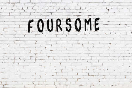 Inscription foursome written with black paint on white brick wall.