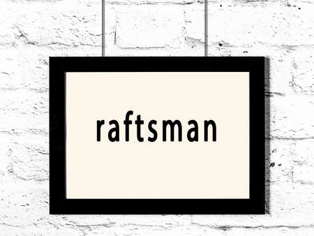 Black wooden frame with inscription raftsman hanging on white brick wall 스톡 콘텐츠
