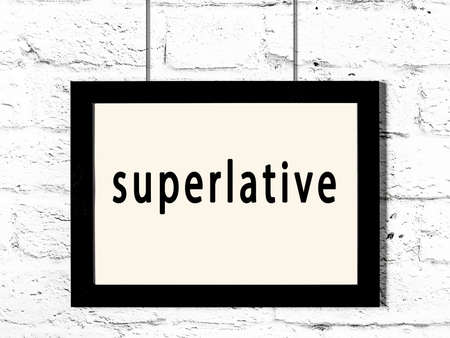 Black wooden frame with inscription superlative hanging on white brick wall 스톡 콘텐츠