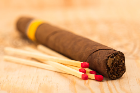 cheroot: One cigar and five matches with red heads on a wooden surface Stock Photo