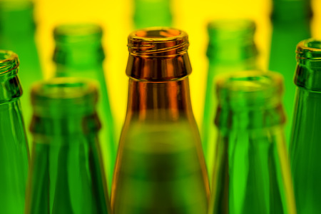 ten empty: Ten empty beer bottles on a yellow background Stock Photo