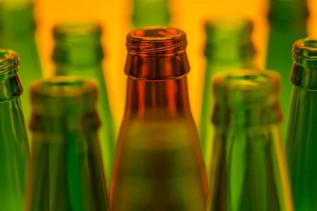 ten empty: Ten empty beer bottles shot with orange light. Nine green bottles and one brown.  Stock Photo