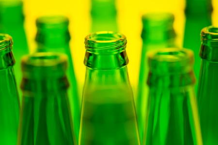 ten empty: Ten green empty beer bottles shot with yellow light  One central bottles in focus  Stock Photo