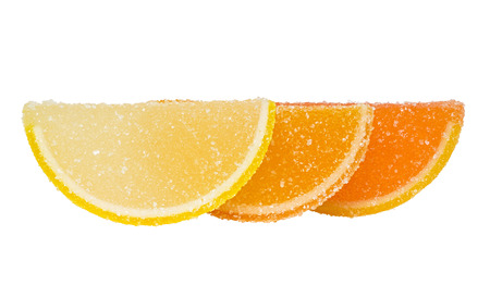 dulcet: Three slices of yellow and orange marmalade sprinkled with sugar, stand one behind another, and are located on a white background.