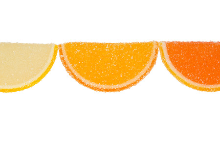 dulcet: Three slices of yellow and orange marmalade sprinkled with granulated sugar on a white background.