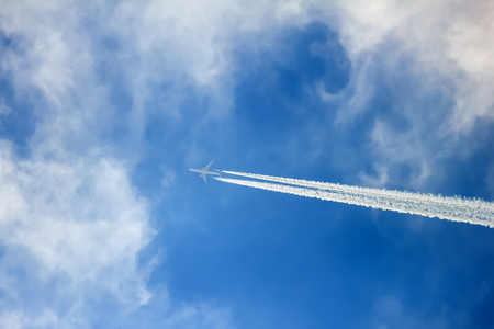 contrail: Silhouette of aircraft flying at high altitudes in the clouds and leaving contrail Stock Photo