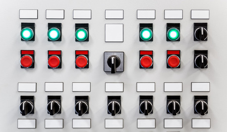 operating key: Control panel of industrial equipment with name plates, switches, red buttons and glowing green buttons