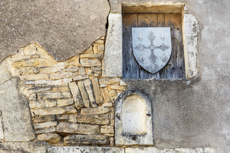 niches: Old stone wall with niches and wooden shield stamp in one of the cities in Burgundy, France Stock Photo